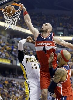 FILE - In this May 7, 2014 file photo, Washington Wizards center Marcin Gortat (4) get a dunks over teammate Drew Gooden, right, and Indiana Pacers center Ian Mahinmi during the first half of game 2 of the Eastern Conference semifinal NBA basketball playoff series, in Indianapolis. (AP Photo/Darron Cummings, File)