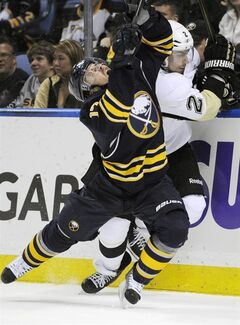 Buffalo Sabres' Linus Omark (17), of Sweden, grimaces after a check on Pittsburgh Penguins' Matt Niskanen (2) during the first period of an NHL hockey game in Buffalo, N.Y., Wednesday, Feb. 5, 2014. Pittsburg won 5-1. (AP Photo/Gary Wiepert)