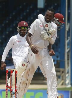 West Indies bowler Sulieman Benn, front, is hugged by captain and wicket keeper Denesh Ramdin, while celebrating the wicket of New Zealand's batsman Jimmy Neesham, who was caught by Benn for 7 runs, during the second innings on the fourth day of their second cricket Test match in Port of Spain, Trinidad, Thursday, June 19, 2014. (AP Photo/Arnulfo Franco)