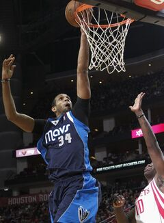 Dallas Mavericks forward Brandan Wright (34) drives for a layup past Houston Rockets forward Ronnie Brewer (10) during the first half of an NBA basketball game, Monday, Dec. 23, 2013, in Houston. (AP Photo/Bob Levey)
