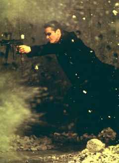 Neo (Keanu Reeves) charges through a hail of gunfire in The Matrix.