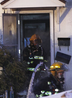 Firefighters extinguish a fire in a two-and-a-half-storey home in the 100 block of St. Cross St. this morning.