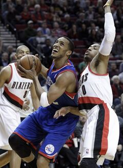 Philadelphia 76ers forward Evan Turner, left, drives on Portland Trails Blazers guard Damian Lillard during the first half of an NBA basketball game in Portland, Ore., Saturday, Jan. 4, 2014. (AP Photo/Don Ryan)