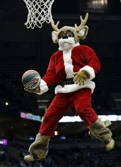 The Milwaukee Bucks mascot Bango goes up for a shot during a break in the second half of an NBA basketball game against the Philadelphia 76ers, Saturday, Dec. 21, 2013, in Milwaukee. (AP Photo/Morry Gash)