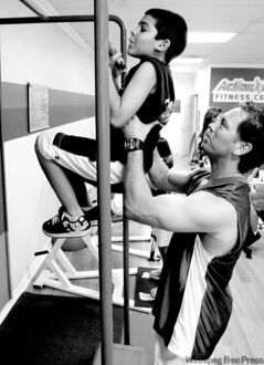 Action Fitness owner Steve Ewing, right, trains  Nathan Soneja, 8, on the pull up bar in Placentia, Calif., Tuesday, Aug. 12, 2008.  It may sound like a grown-up workout, but more parents are turning to gyms to make sure their children get some exercise.    (AP Photo/Chris Carlson)