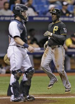 Pittsburgh Pirates' Starling Marte, right, scores in front of Tampa Bay Rays catcher Ryan Hanigan on an RBI single by Andrew McCutchen off Rays pitcher Alex Cobb during the third inning of an interleague baseball game Monday, June 23, 2014, in St. Petersburg, Fla. (AP Photo/Chris O'Meara)