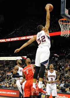Atlanta Hawks forward Mike Scott (32) dunks over Houston Rockets' Aaron Brooks (0) in the first half of an NBA basketball game on Friday, Jan. 10, 2014, in Atlanta. (AP Photo/David Tulis)