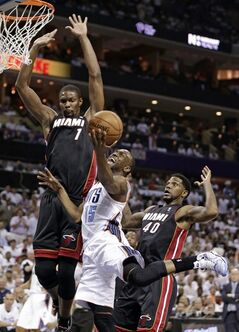 Charlotte Bobcats' Kemba Walker (15) is fouled as he drives between Miami Heat's Chris Bosh (1) and Udonis Haslem (40) during the first half in Game 3 of an opening-round NBA basketball playoff series in Charlotte, N.C., Saturday, April 26, 2014. (AP Photo/Chuck Burton)