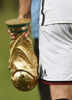 Germany's Toni Kroos walks with the trophy after the World Cup final soccer match between Germany and Argentina at the Maracana Stadium in Rio de Janeiro, Brazil, Sunday, July 13, 2014. Germany won the match 1-0. (AP Photo/Martin Meissner)