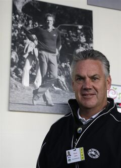 Steve John, CEO of the Monterey Peninsula Foundation and tournament director of the AT&T Pebble Beach Pro-Am golf tournament, poses beneath a photograph of Clint Eastwood Friday, Feb. 7, 2014, in Pebble Beach, Calif. John was choking on a piece of cheese at a volunteer party when Eastwood gave him the Heimlech maneuver, Wednesday evening, Feb. 5, at the Monterey Conference center in Monterey, Calif. (AP Photo/Eric Risberg)