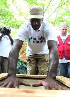 Michael Jordan puts his hands in cement to leave hand prints in the court yard of Hornets Nest Elementary School as a part of the Hornets all-staff Day of Service on Monday, June 9, 2014. (AP Photo/The Charlotte Observer, Isabella Bartolucci)