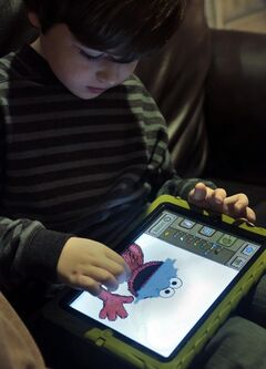 In this Tuesday, Dec. 3, 2013, photo, Marc Cohen, 5, uses a Sesame Street app on his tablet at home in New York. Tablets of all types are expected to rank among the top holiday gifts for children this year, but some experts and advocates question the educational or developmental benefits for youngsters. (AP Photo/Bebeto Matthews)