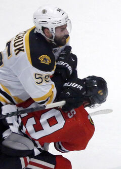 Chicago Blackhawks center Jonathan Toews, bottom, takes a hit from Boston Bruins defenseman Johnny Boychuk during the second period in Game 5 of the NHL hockey Stanley Cup Finals in Chicago on Saturday.