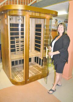 Arctic Spas owner Liz Seymour with The Stockholm, a two-person infrared sauna available in cedar or hemlock for about $2,900.