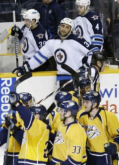Dustin Byfuglien looks on as the Nashville Predators celebrate an overtime win Oct. 24 in Nashville. Care to guess which player turned over the puck to set up the game-winning goal?