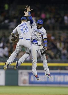 Toronto Blue Jays' Brett Lawrie, left, and Jose Reyes celebrate after Toronto's 5-3 win over the Detroit Tigers in a baseball game in Detroit, Tuesday, June 3, 2014. (AP Photo/Carlos Osorio)