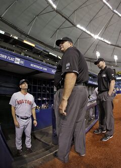 Crew chief Jerry Layne, center, and Mike Estabrook, right, talk to Boston Red Sox bench coach Torey Lovullo about a delay in the Red Sox's baseball game against the Tampa Bay Rays on Saturday, Aug. 30, 2014, in St. Petersburg, Fla. Lightning outside the stadium knocked out some of the power. The game was delayed about 10 minutes. (AP Photo/Chris O'Meara)