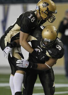 Manitoba Bisons' Alex Vitt (left) and Nic Demski celebrate Demski's touchdown against the Saskatchewan Huskies in the second half of the Canada West semi-final at Investors Group Field Friday.