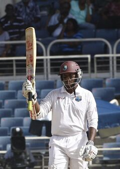 West Indies batsman Shivnarine Chanderpaul raises his bat after scoring a half century during the third day of their first cricket Test match against New Zealand in Kingston, Jamaica, Tuesday, June 10, 2014. (AP Photo/Arnulfo Franco)