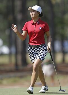 Minjee Lee, of Australia, holds up her ball after making a putt on the 12th hole during the second round of the U.S. Women's Open golf tournament in Pinehurst, N.C., Friday, June 20, 2014. (AP Photo/Bob Leverone)