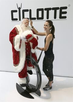 Actor Brady White, left, portrays Santa Claus as model Jalane Lindle wipes his brow as they demonstrate the Ciclotte during the unveiling of the gifts included in the Neiman Marcus Christmas Book Tuesday, Oct. 8, 2013, in Dallas. The Ciclotte is an exercise bike on sale for $11,000. (AP Photo/LM Otero)