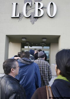 Patrons line up to get into an LCBO outlet to buy their New Year's Eve beverages in this file photo.