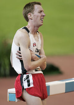Canada's Matthew Kerr sits on an obstacle as he tries to catch his breath after placing eighth in the 3000m steeplechase at the XVIII Commonwealth Games in Melbourne, Australia, Friday March 24, 2006.(CP PHOTO/Adrian Wyld)