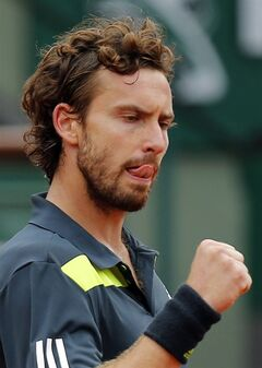 Latvia's Ernests Gulbis clenches his fist as he plays Switzerland's Roger Federer during their fourth round match of the French Open tennis tournament at the Roland Garros stadium, in Paris, France, Sunday, June 1, 2014. (AP Photo/David Vincent)
