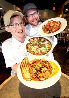 Head Chef Shaun Ursell, front, displays Manila Clams with chorizo sausage and artichokes and Chicken Pesto Pizza and Sous Chef Sean McKay with Linguini with clams, sea scallops, prawns, fish and asparagus in marinara sauce.