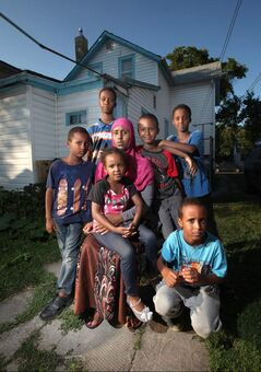 Idil Timayare and her six children at home in the North End. She holds daughter, Samira, and is surrounded by sons (from left) Salman, Zakariya, Soyan, Harrun and Ahmed (kneeling).