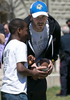 Blue Bombers QB Buck Pierce discusses football strategy with 10-year-old Tom Ali on the U of W campus Wednesday afternoon.