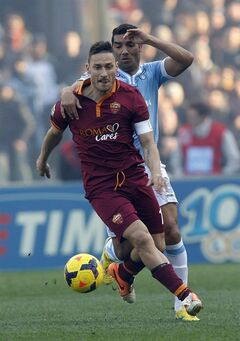 AS Roma forward Francesco Totti, is chased by Lazio's Andre Dias during an Italian Serie A soccer match between Lazio and AS Roma at Rome's Olympic stadium, Sunday, Feb. 9, 2014. (AP Photo/Alessandra Tarantino)