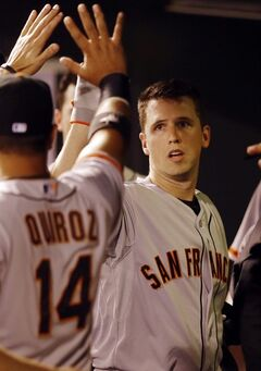 San Francisco Giants' Buster Posey high fives teammate Guillermo Quiroz after hitting a solo home run off Colorado Rockies starting pitcher Jordan Lyles during the sixth inning of a baseball game Tuesday, Sept. 2, 2014, in Denver. (AP Photo/Jack Dempsey)