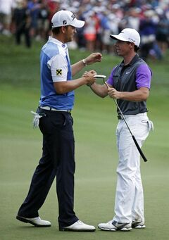 Rory McIlroy, of Northern Ireland, right, greets Bernd Wiesberger, of Austria, after winning the PGA Championship golf tournament at Valhalla Golf Club on Sunday, Aug. 10, 2014, in Louisville, Ky. (AP Photo/John Locher)
