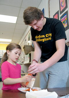 Taylor, a Grade 2 student at École Riverbend Community School, prepares a veggie wrap with help from Garden City Collegiate Grade 12 student Philipp Graeff. Graeff was one of a group of Garden City students who visited the elementary school last week to teach the kids about proper nutrition.
