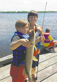 A young angler from Centennial School holds a pike he caught.