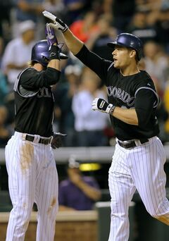 Colorado Rockies' Justin Morneau, right, is congratulated by Charlie Blackmon after hitting a two run home run off Miami Marlins starting pitcher Henderson Alvarez during the third inning of a baseball game Friday, Aug. 22, 2014, in Denver. (AP Photo/Jack Dempsey)