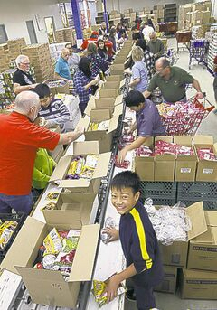 JOE BRYKSA / WINNIPEG FREE PRESS Eldrick Ausria (front), helps pack hampers.