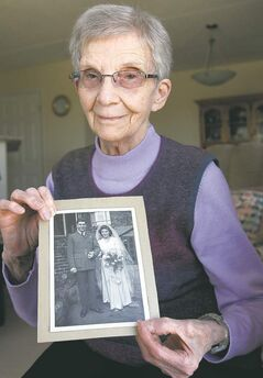 Rose Lindsay holds a photo of their wedding in 1945.