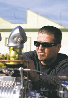 Jimmy Shine, shop manager at So-Cal Speed Shop, checks the flathead Ford engine on his 1934 Ford hot rod pickup.