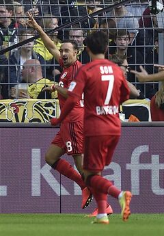 Leverkusen's Karim Bellarabi celebrates after scoring during the German Bundesliga soccer match between Borussia Dortmund and Bayer Leverkusen in Dortmund, Germany, Saturday, Aug. 23, 2014, 2014. (AP Photo/Martin Meissner)