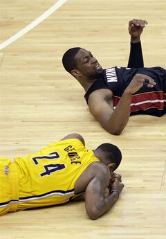 In this Tuesday, May 20, 2014, photo, Indiana Pacers guard Paul George, bottom, lies on the floor after being struck in the head by the knee of Miami Heat guard Dwyane Wade, top, during the second half of Game 2 of the NBA basketball Eastern Conference finals in Indianapolis. George has a concussion, and it's unclear when he will return to practice or whether he will play Saturday night against Miami. (AP Photo/AJ Mast)
