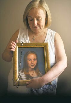 Elaine Stevenson holds a portrait of her daughter Alyssa, with a rosary draped across it.
