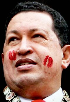 Kiss marks left by supporters of Venezuela's former President Hugo Chavez cover a photograph of him hanging on a wall near a book store during the annual book fair in Caracas, Venezuela, Tuesday, March 19, 2013.