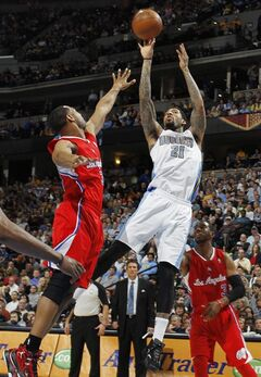 Los Angeles Clippers guard Chris Paul, left, tries to block a shot by Denver Nuggets forward Wilson Chandler in the fourth quarter of the Nuggets' 107-92 victory in an NBA basketball game in Denver on Thursday, March 7, 2013. (AP Photo/David Zalubowski)