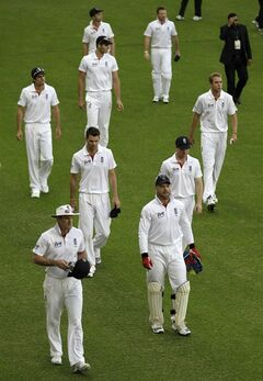 England's captain Andrew Strauss, front left, leads his team off the field of play after being defeated by Pakistan on the third day of the first cricket test match of a three match series between England and Pakistan at the Dubai International Cricket Stadium in Dubai, United Arab Emirates, Thursday, Jan. 19, 2012. (AP Photo/Hassan Ammar)