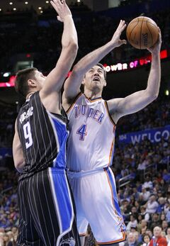Orlando Magic center Nikola Vucevic (9) defends as Oklahoma City Thunder's Nick Collison (4) goes up for the basket during the fourth quarter of an NBA basketball game in Oklahoma City, Friday, March 15, 2013. Oklahoma City won 117-104. (AP Photo/Alonzo Adams)