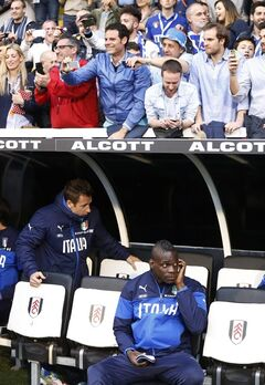 Italy's Mario Balotelli, lower right, looks on from the dugout as supporters, top, watch the players arrive at the dugout before the start of their international friendly soccer match against Republic of Ireland at Craven Cottage, London, Saturday, May 31, 2014. (AP Photo/Sang Tan)