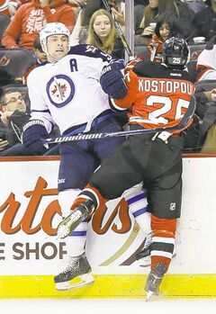Winnipeg Jets' Mark Stuart and New Jersey Devils' Tom Kostopoulos collide in the first period.
