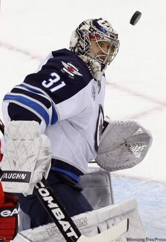 Winnipeg Jets goalie Ondrej Pavelec keeps his eye on the puck as he makes a save against the New Jersey Devils during the second period of their NHL game in Newark, N.J., Tuesday.